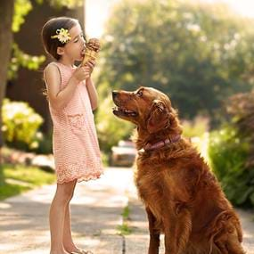 Girl eating ice cream cone with dog