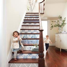 Arhaus children playing on blue and white wallpaper stairs